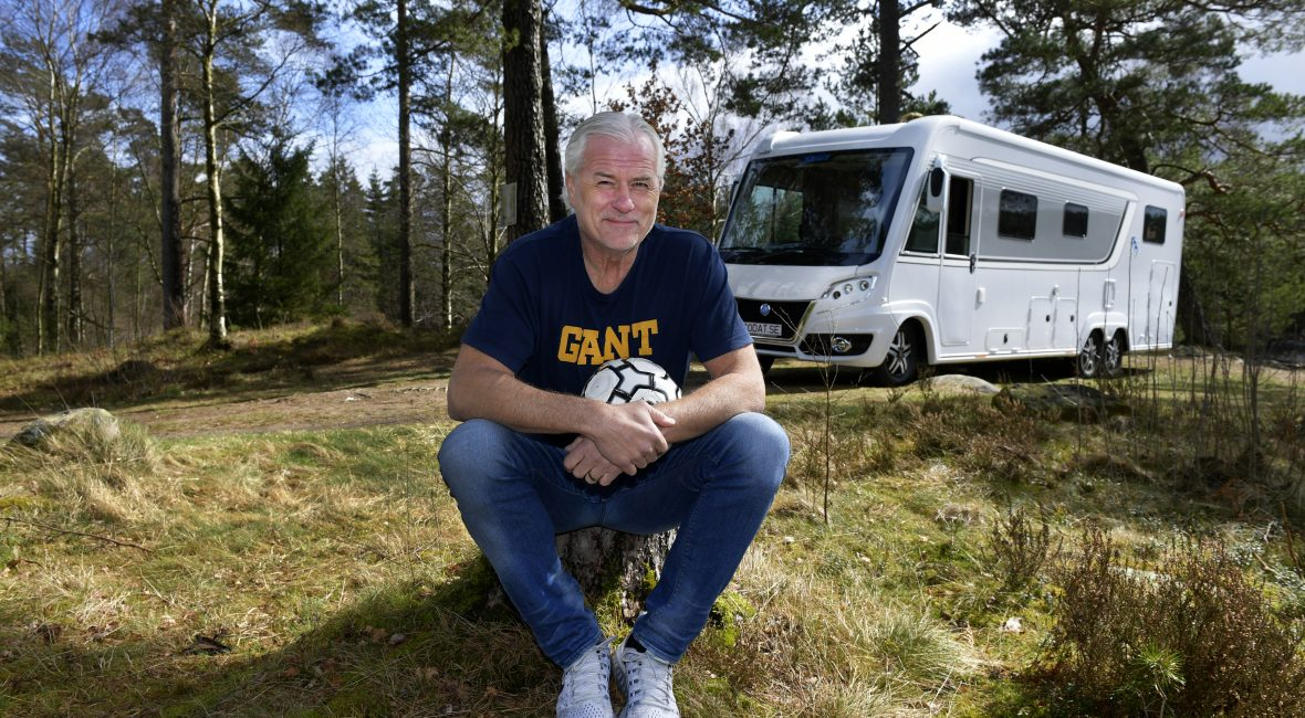 Glenn Hysén sittandes framför en husbil ute i naturen