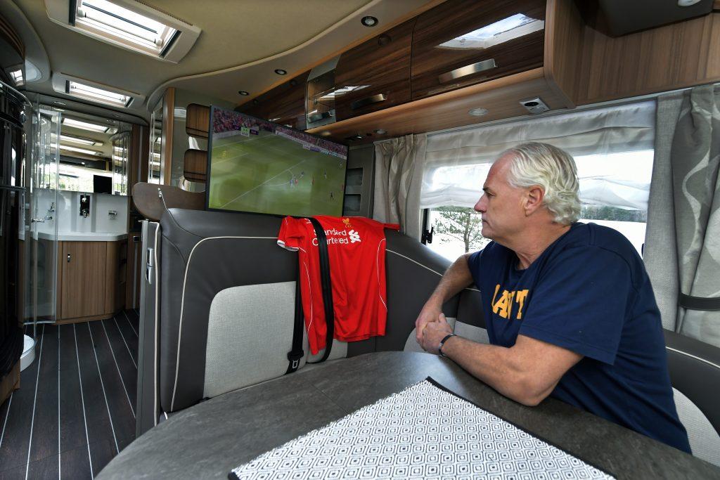 Glenn Hysén sitter i husbil och tittar på tv:n där fotboll visas