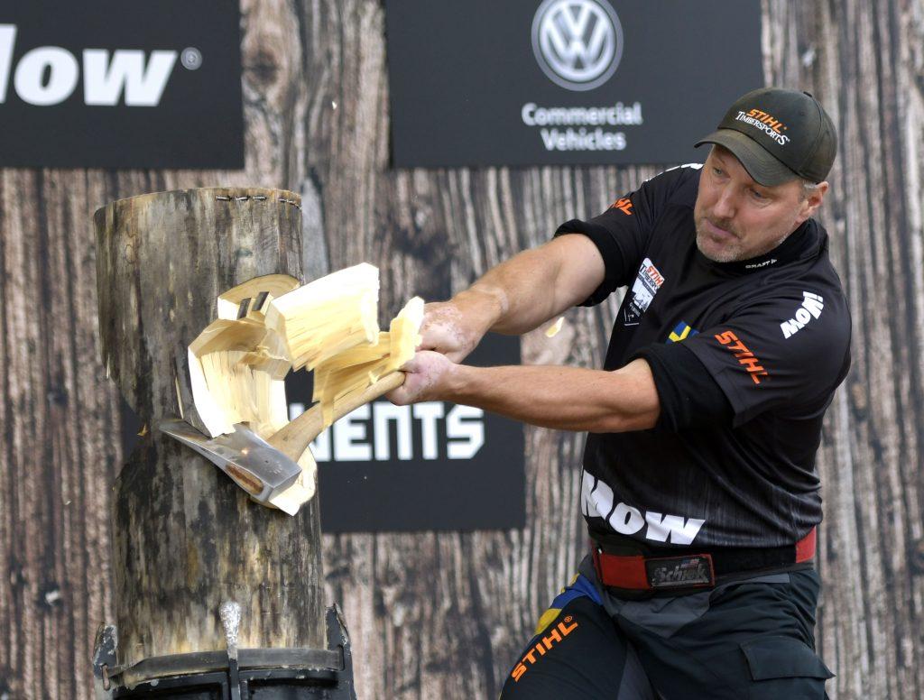 Bild från tävlingarna i Timbersports. En man hugger med yxa i ett träblock.