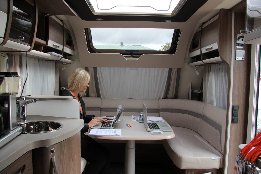 Bild från inuti husvagnen. En kvinna arbetar vid en dator sittandes i den soffa som finns i husvagnens främre del.