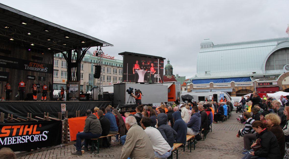 Vy över Kungstorget i Göteborg. Åskådare sitter på bänkar framför en scen och i bakgrunden står en husvagn.