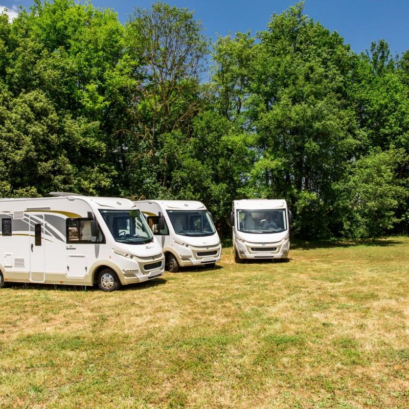 Tre helintegrerade husbilar av Modellen Magis står på en gräsmatta. Husbilarna är vita med ljust mönster, det är blå himmel och i bakgrunden finns träd
