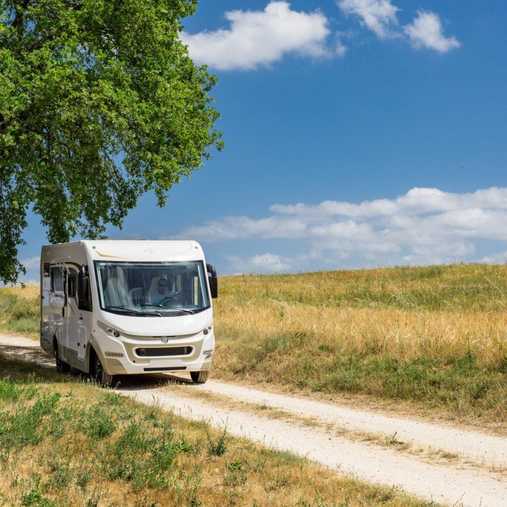 Bild tagen framifrån på en helintegrerad husbil som kör på en väg med stora fält runt om kring. Det är fint väder och blå himmel.