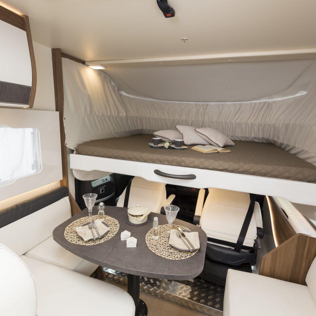 Bild tagen i en husbil. Bilden visar en neddragen fällsäng, ett bord och en bit av en sittgrupp längst fram i fordonet.