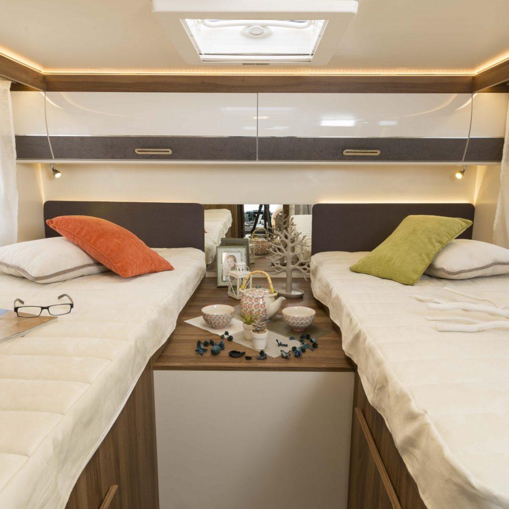 Bild tagen inuti en husbil. i vardera kant av fotot är en säng. I mitten en förvaringsyta och i taket ett takfönster.