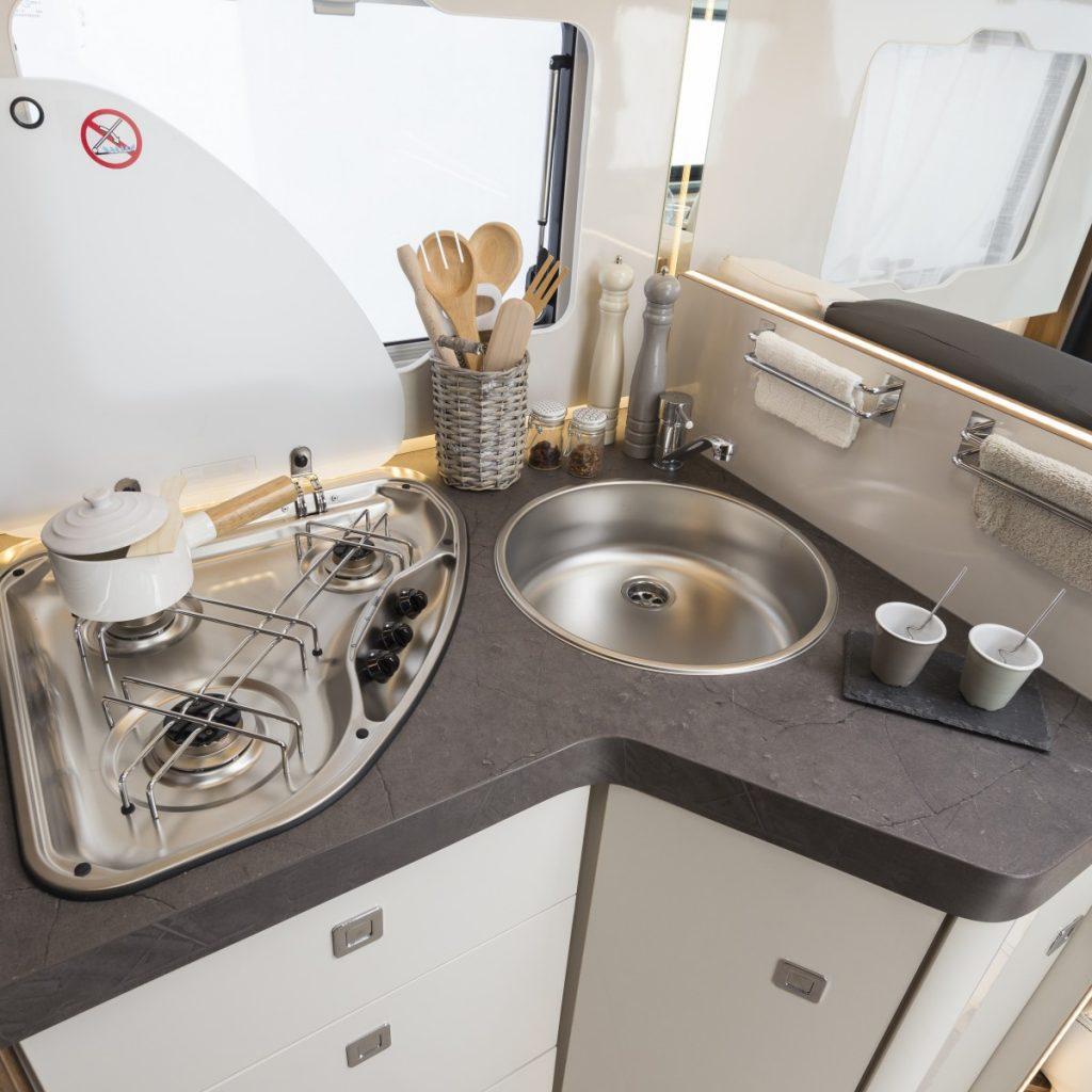 Bil på ett kök i en husbil, bilden är tagen snett ovanifrån . Det finns en spis med tre något, en diskho och flertalet lådor.