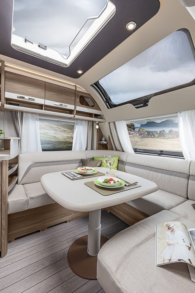 Exempel på husvagn med stort panoramafönster och rymlig sittgrupp fram.