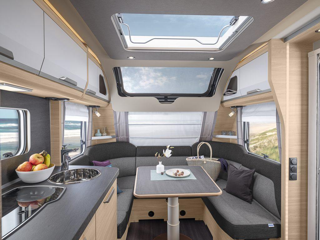 Bild tagen inuti en husvagn. Rakt fram finns en  u-formad soffa med ett bord i mitten. Över soffan finns ett stort fönster och till vänster syns ett kök.