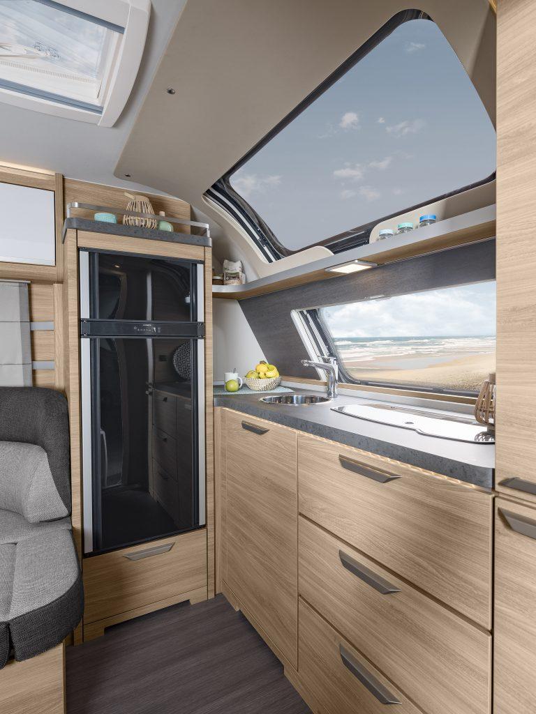 Bild på frontkök i husvagn. Längst bort i bild finns ett stort kylskåp, mot fronten finns ett fönster, en diskho, spis och bänkyta