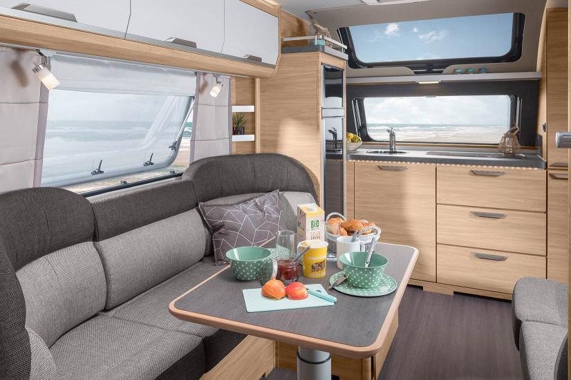 Bild från inuti en husvagn. Närmast syns delar av en soffgrupp och ett dukat bord. Längre bort syns kylskåp, frontkök havet genom fönstret i vagnens front.