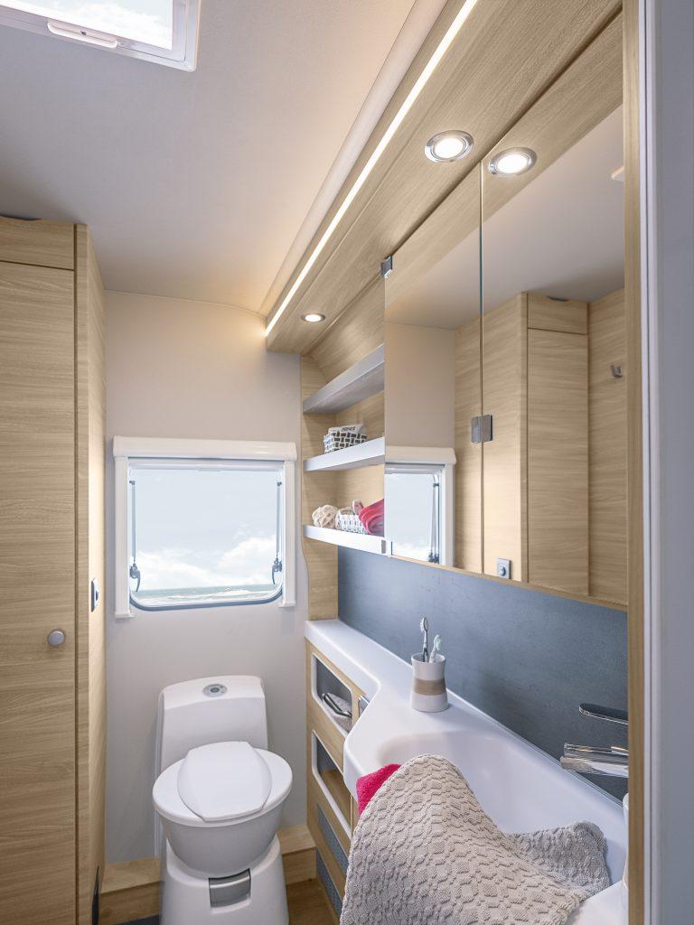 Bild från badrummet i husvagnen.  Längst bort en toalettstol med ett fönster ovanför. Till höger handfat och avställningsyta samt hyllor och spegelskåp.