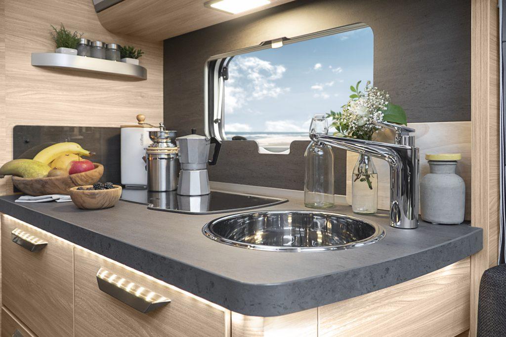 Närbild på kök i husvagnen. Grå bänkskiva på vilken det står en fruktskål, en liten kaffebryggare och blommor. Över köksbänken finns ett fönster.