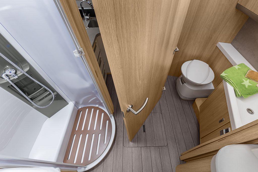 Vy över badrummet snett ovanifrån. Till vänster en duschkabin, rakt fram en dörr som kan stängas antingen framåt eller åt höger. Till höger finns toalett och handfat.