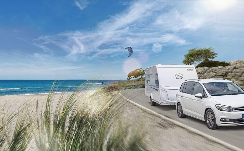 En vit bil med en husvagn kör på en väg längs med stranden, till vänster syns havet. Det är blå himmel och sommar.